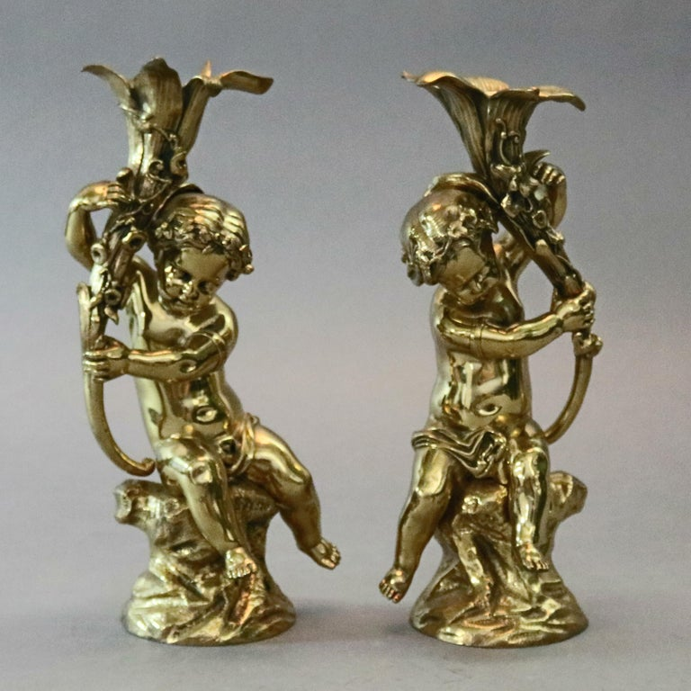 An antique pair of French Classical candlesticks offer cast and gilt bronze figural sculptures of cherbi with lily form candle sockets, circa 1880.  Measures: 11