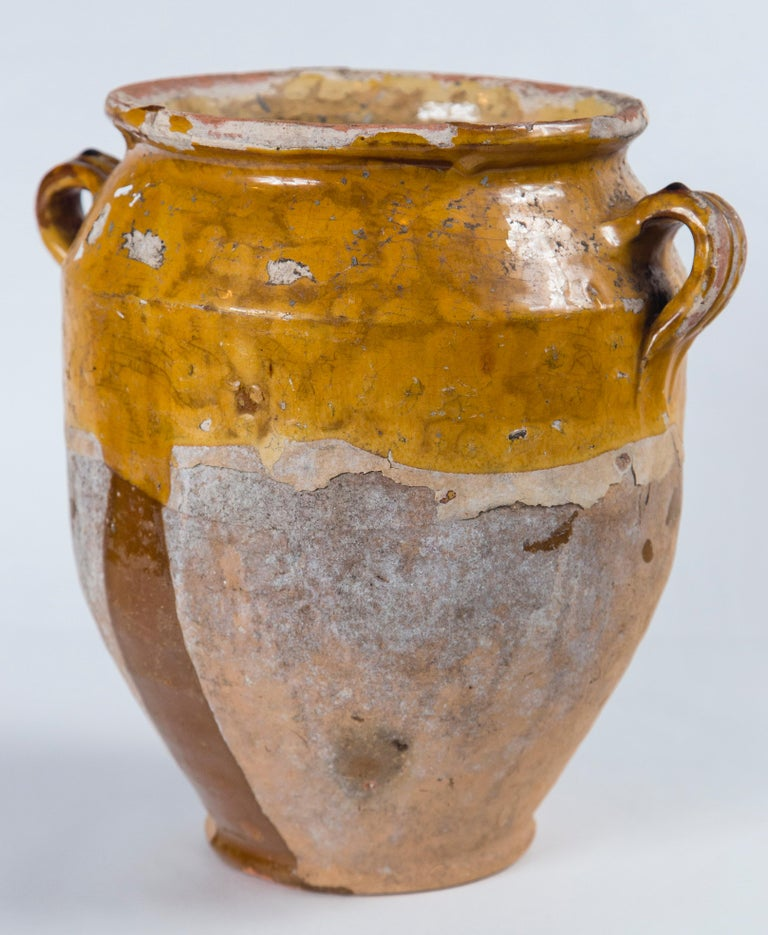 Antique French confit pot, circa 1900. Aged terra cotta with yellow glaze. Confit pots were used for food preservation. The bottom half was left unglazed to allow the pot to keep cool while half buried in the ground.