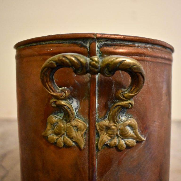 A long and heavy antique French copper potted plant holder, with a beautiful rich patina, circa early 1900s.   Four round openings meant to hold terracotta pots, are cut into the top. The holder has rounded ends showing ornate floral brass side