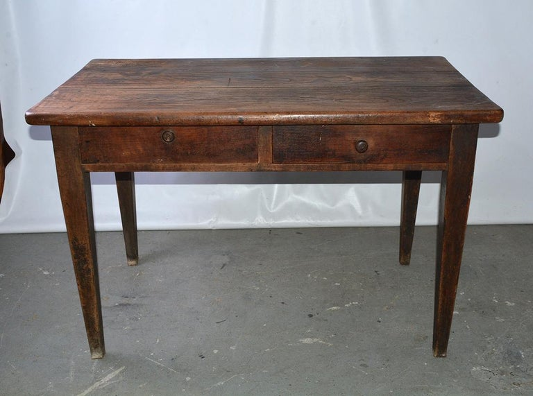 The rustic antique country desk, writing table or server made of chestnut has two deep, dovetailed drawers. The right one has a wooden pull and the left one has a lock and key. The legs are straight and beautifully tapered. The desk's simplicity