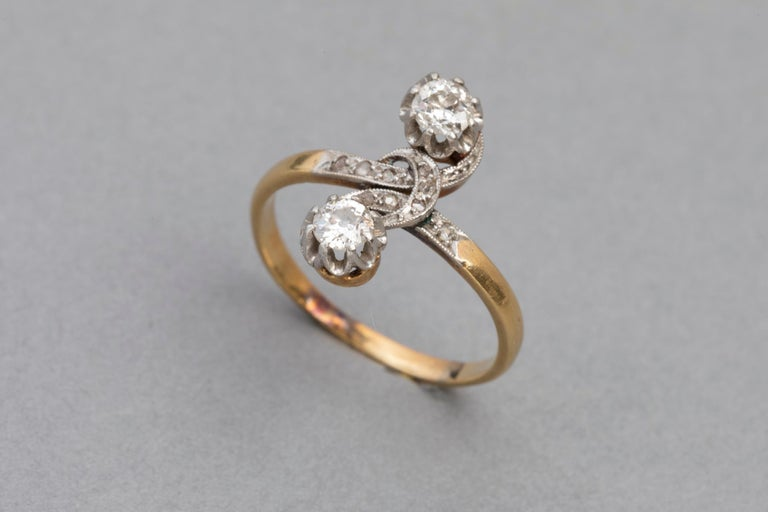 Very lovely antique ring. Crossover or Toi et moi shape designed.  Made in France circa 1910 (edwardian? )  Mounted with yellow gold 18k and platinum  (French control marks: Owl and Old man)  Set with two beautiful Round old european curt diamonds