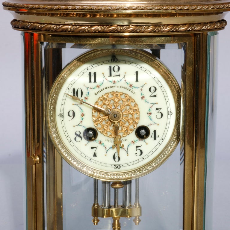 An antique French Medaille D'argent regulator clock retailed by Bailey, Banks and Biddle of Philadelphia, Pennsylvania (PA) offers brass and crystal case with floral decorated and retailer signed enameled face having Arabic numerals, 1889 Medaille