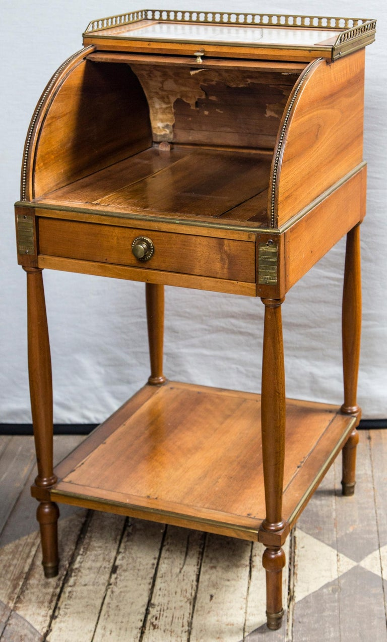 Made of fruit wood with a marble top (cracked). Brass gallery surrounds the marble top. Brass pulls and mounts. The inside of the top shows old canvas and paper.
