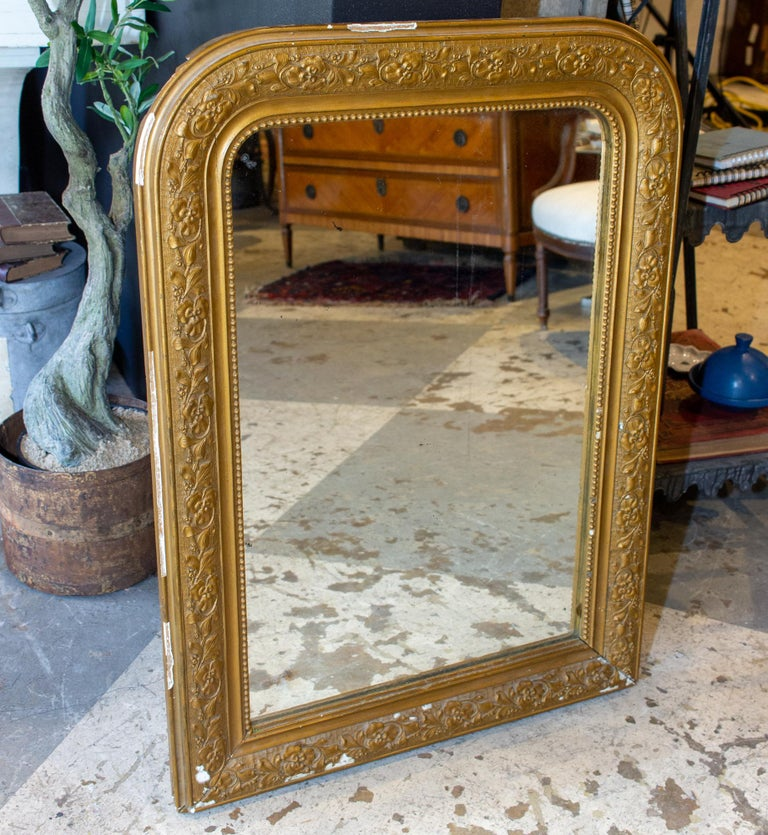 This antique French Louis Philippe mirror has a distressed gold finish with a raised floral pattern molding along the center of the frame and a beaded interior edge. The flowers appear to be pansies. Mirror is in good condition, with some spotting