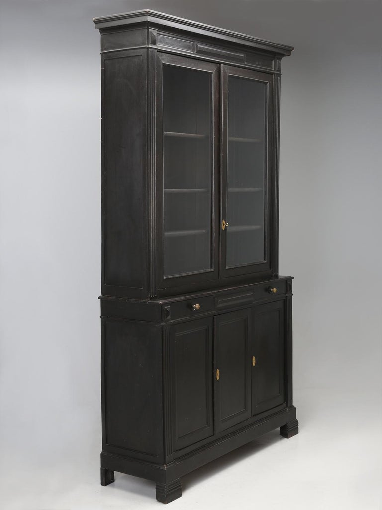 An original ebonized bookcase, bibliotheque, display or china cabinet and by the word original, we are referencing, that this is not a newly doctored up antique French black cabinet, painted to look ebonized, but rather, a 100%, untouched, all