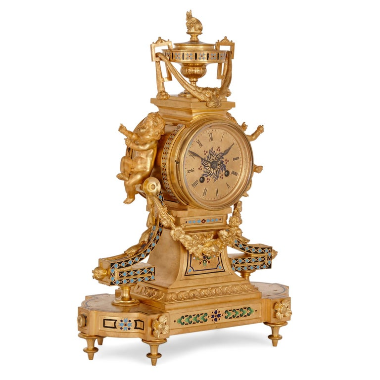 Antique French eclectic style enamel and gilt bronze clock set French, late 19th century Measures: Clock: Height 41cm, width 30cm, depth 15cm Candelabra: Height 36cm, width 17cm, depth 17cm  This gilt bronze and enamel garniture contains a
