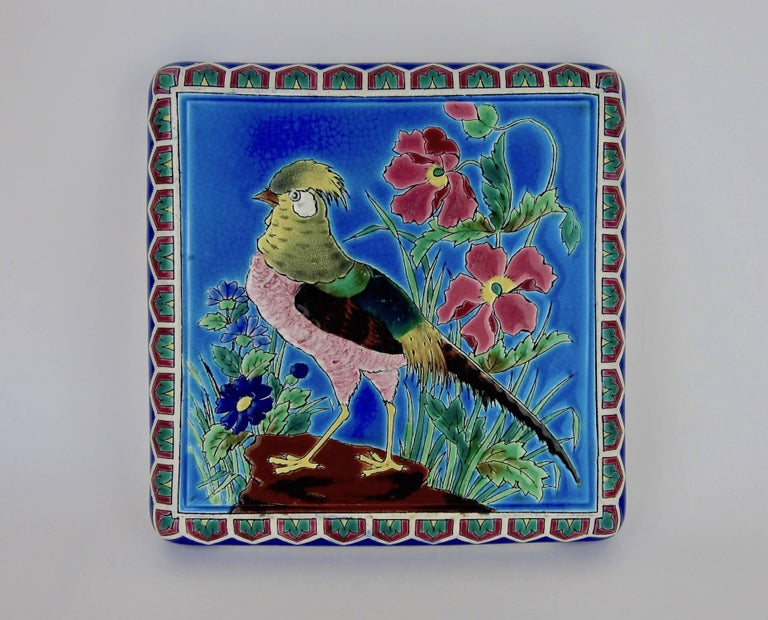An antique French faience stand or trivet from the Emaux de Longwy art pottery workshop in France. The decorative ceramic platter rests on four feet and can be displayed on a tabletop or desk. The underside of the piece is marked with hand painted