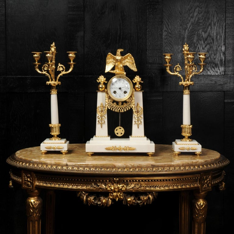 A stunning original antique French clock set circa 1890. It is of Empire design in crisp white Carrera marble and ormolu (finely gilded bronze). To the top is a beautifully modelled spread eagle with flaming finals to the sides. The clock is