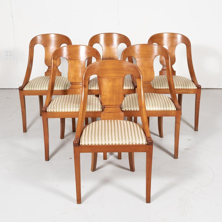 A wonderful and very comfortable set of six classic French Empire style Gondola dining chairs from the Bordeaux region, in solid cherry with a lustrous French polish, circa early 1900s. Each chair is beautifully carved with a curving back having urn