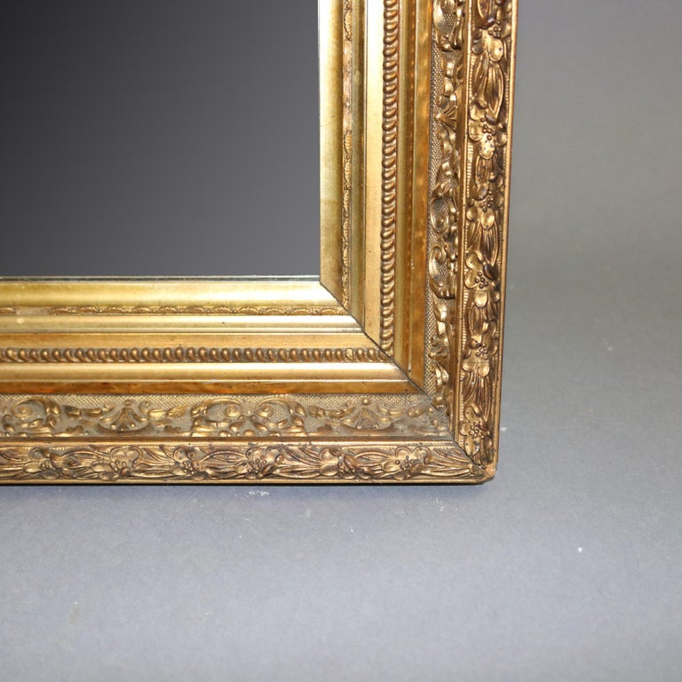 An antique French first finish giltwood framed mirror offers foliate and floral relief pattern surround, 19th century   ***DELIVERY NOTICE – Due to COVID-19 we are employing NO-CONTACT PRACTICES in the transfer of purchased items.  Additionally, for