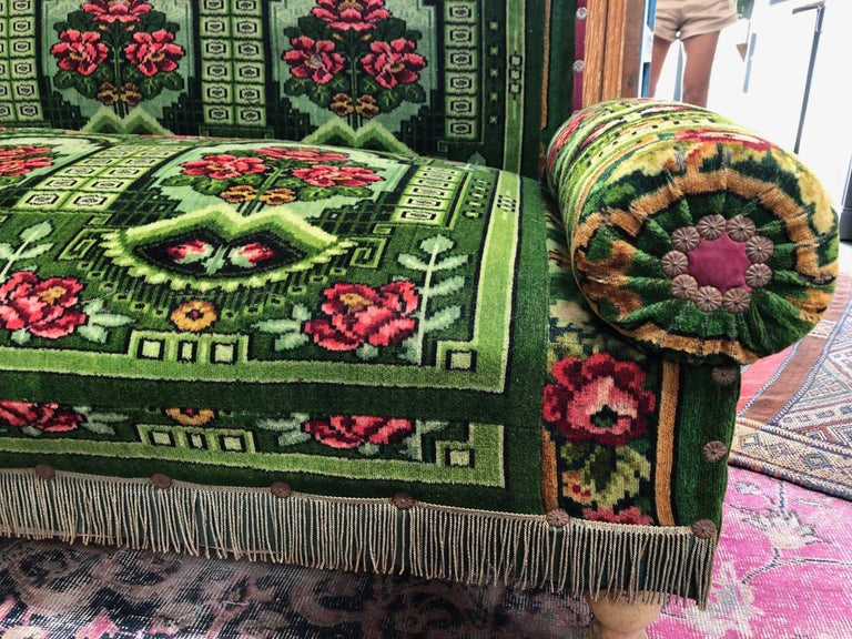 This antique French floral settee is upholstered with a vibrant green fabric featuring a floral pattern and embellishments, adding elegance and classic beauty to any home. Arms and backing are both removable which makes storing and rearranging