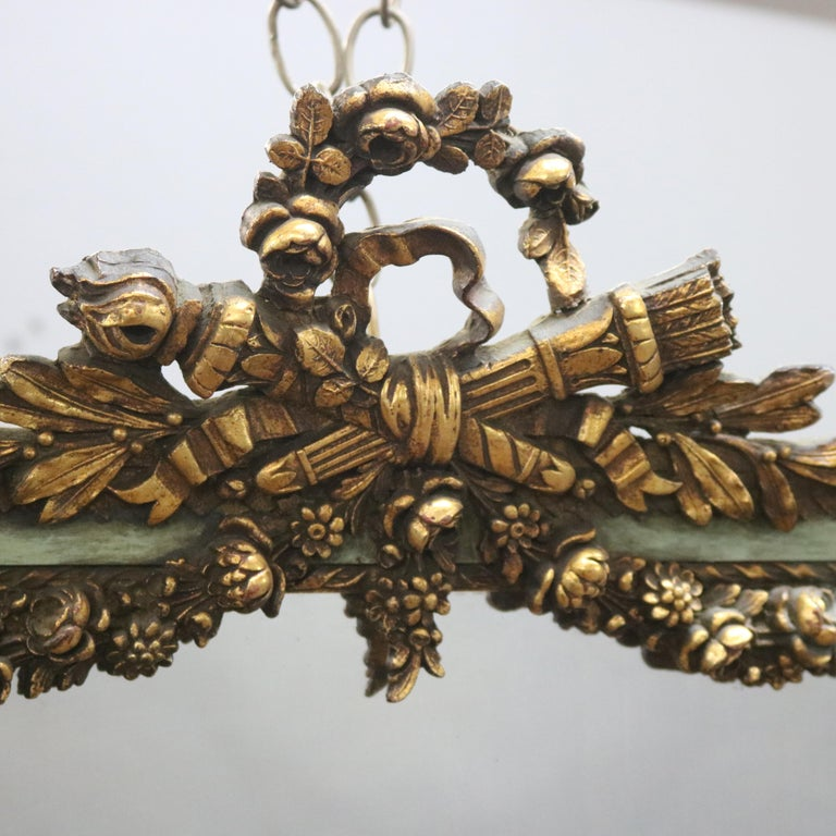 An antique French wall mirror offers giltwood frame with pierced floral wreath crest and swags, 19th century  ***DELIVERY NOTICE – Due to COVID-19 we are employing NO-CONTACT PRACTICES in the transfer of purchased items.  Additionally, for those who
