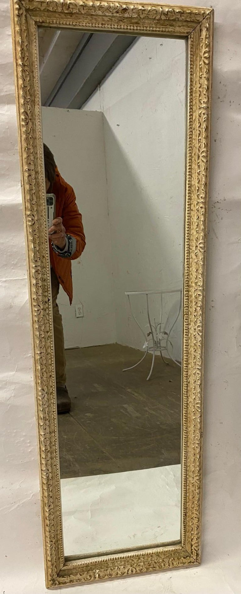 A slender and tall antique French wall mirror with scrollwork design.