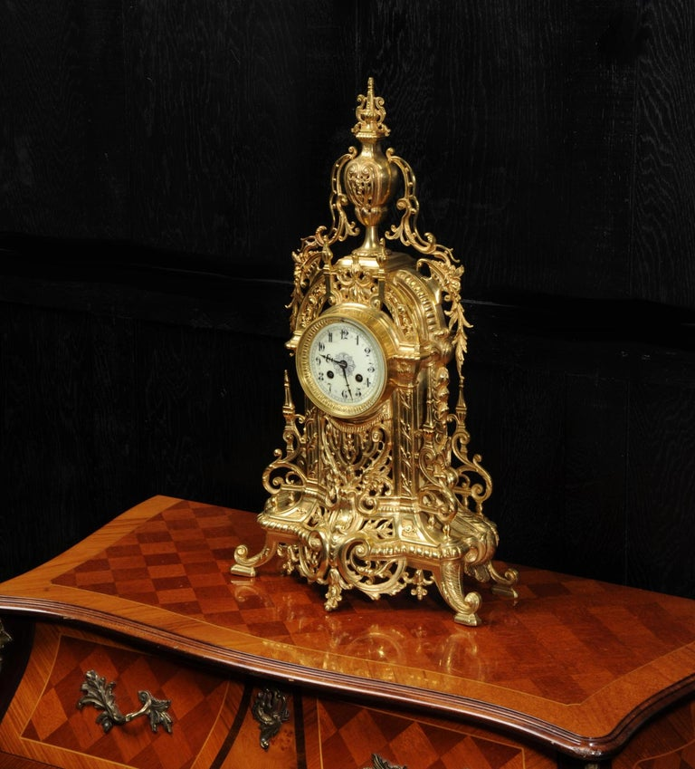 A large and stunning original antique French clock by A.D. Mougin, circa 1900. It is beautifully made from gilded bronze in the Baroque style. It is modeled with profuse, stylized acanthus with the front delicately fretted to allow a glimpse of the