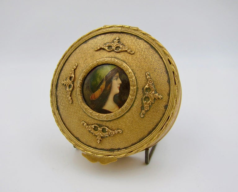 An antique French gilt bronze dresser or vanity box of circular form with an inset hand-painted enamel portrait miniature of a woman in profile. The Limoges-style portrait plaque is encircled by a bronze doré laurel leaf border framed by four