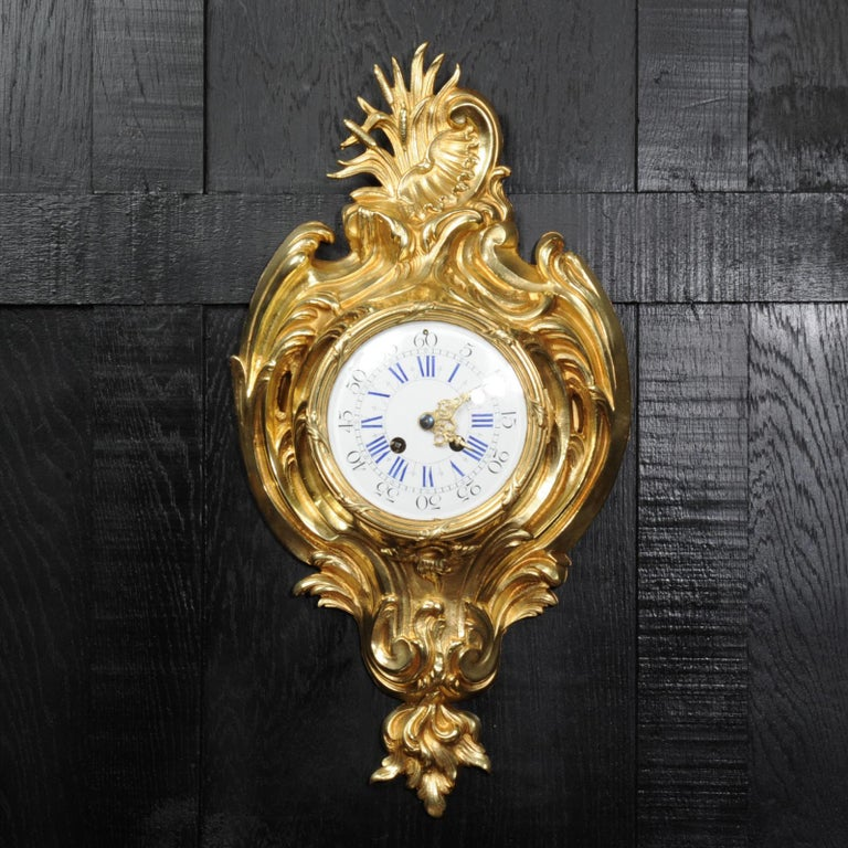 A beautiful original antique French cartel wall clock, circa 1890. It is finely made in gilt bronze in the Rococo style. It is formed of flowing scrolls and acanthus with an elaborate asymmetric C-scroll and shell motif to the top. It is in stunning