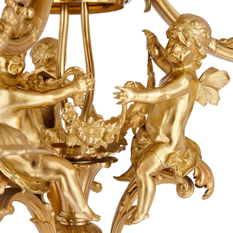 Designed during the sumptuous Belle Époque, this gilt bronze chandelier demonstrates the very best of the period.  The chandelier is supported by a central highly ornate gilt bronze stem. This stem supports the three light branches, each C-scroll
