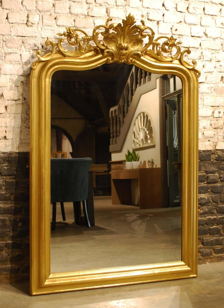 This beautiful antique Louis Philippe mirror was made in Southern France and dates circa 1850. The frame is partly gold leaf gilt and partly gilded with gold paint. The sculpted cartouche or crest on top is centered upon two stylized acanthi