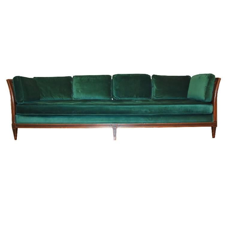 Beautiful green velvet sofa with square back and side pillows. Sides and back feature beautiful cane. Button tufted (or biscuit tufted) bottom cushion extends the entire width of the sofa. In great condition. Small chip on one of the back legs, but