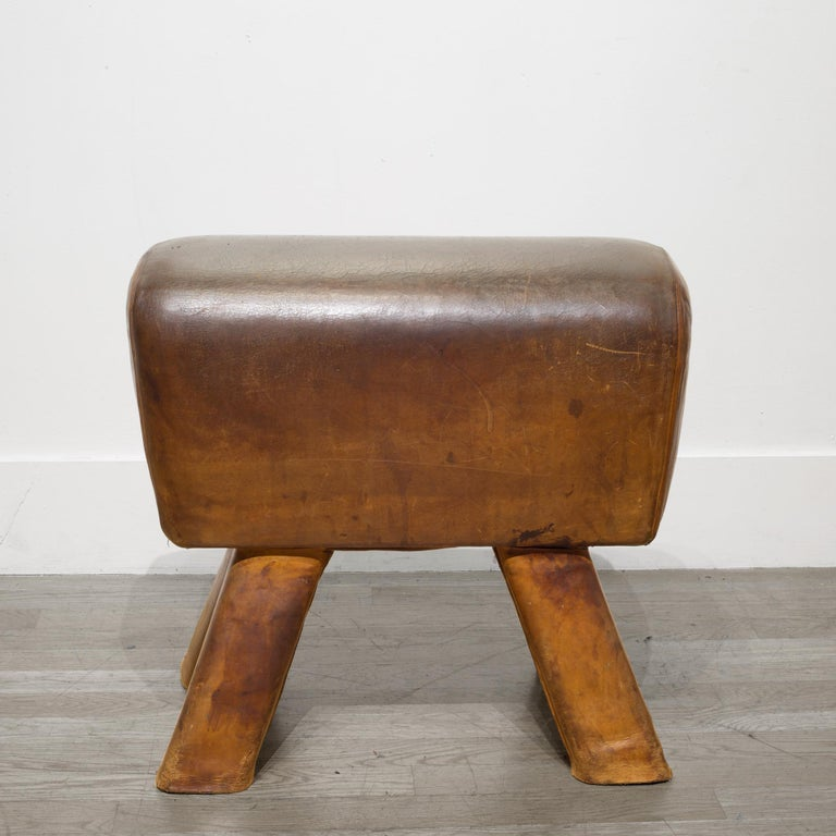 About  This is an original French leather gymnasium pommel horse with four angled legs. Beautifully aged leather with leather wrapped wooden legs. This sturdy piece is excellent condition and can be used as a stool for extra seating.  Creator