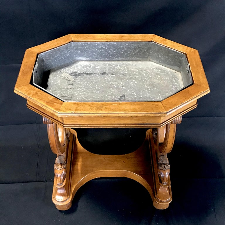 A late 19th century free standing French carved walnut planter table with incredible sheepshead figural feet. The removable zinc planter tray is inset into a boxed walnut top which tapers down to a decorative base highlighting the four exquisitely