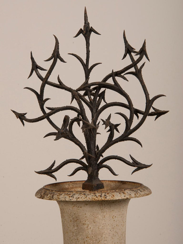 An antique French cast iron urn of campagna form from France circa 1880 with a hand forged iron bush of spikes. Reminiscent of the enchanted hedge that surrounded sleeping beauty as well as the castle of the beast in Jean Cocteau's famous movie