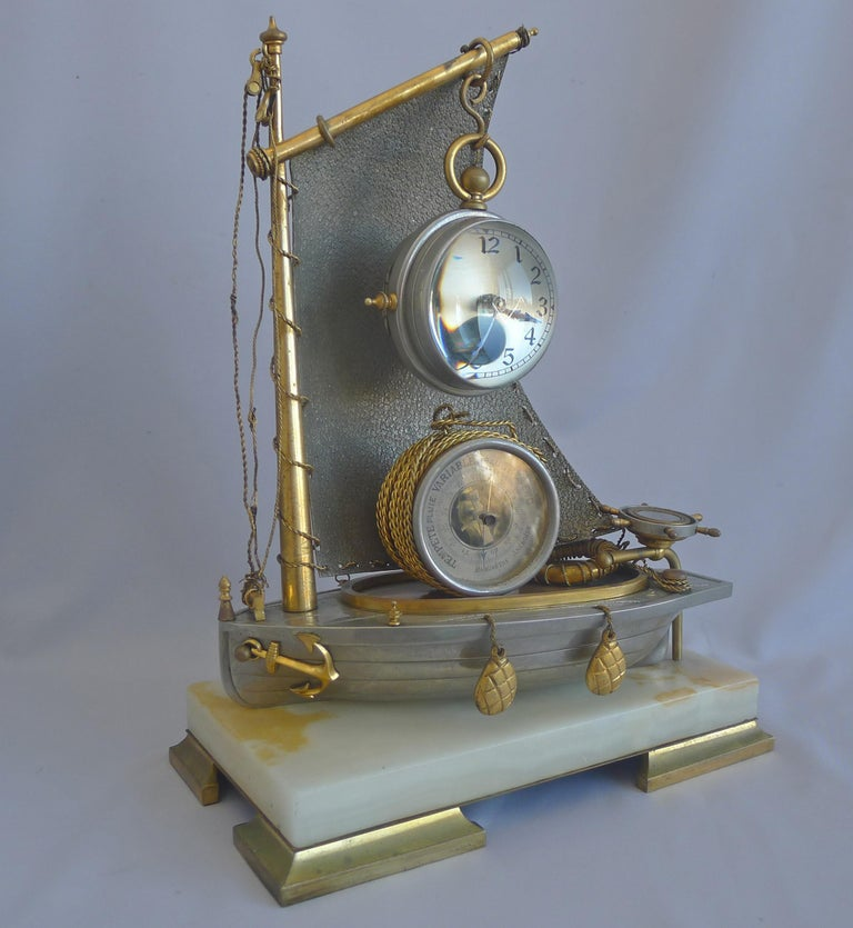 A very rare antique French Industrial series 'Sailboat' compendium clock. Set on four gilt bronze feet and a white onyx base. The silvered bronze hull of the boat with two gilt bronze bouys hanging on the side, as well as the anchor, also in gilt