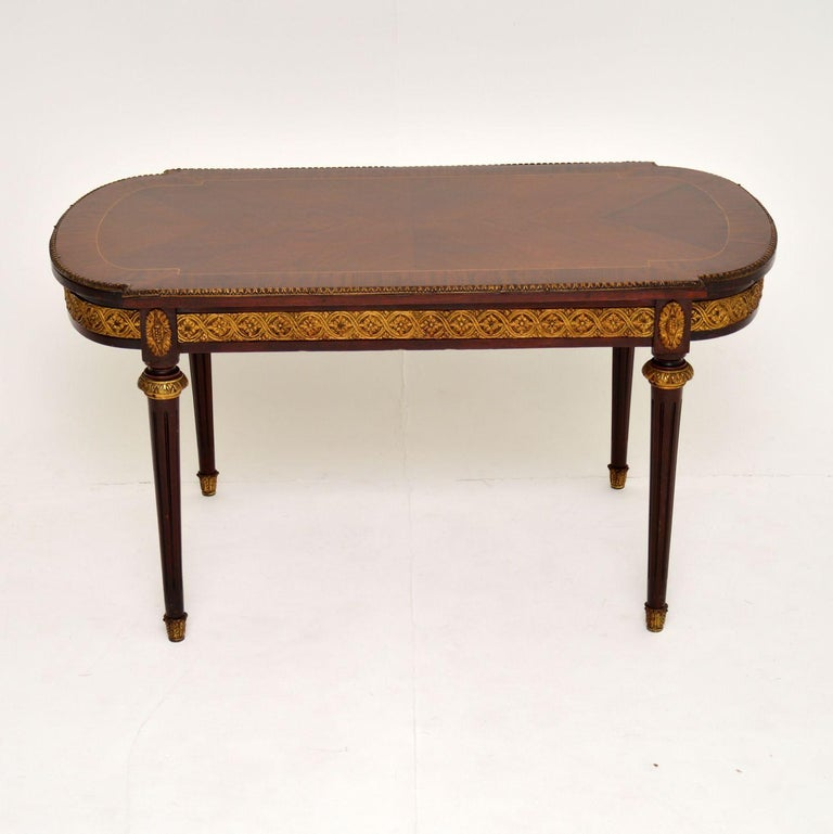 Antique French style mahogany and kingwood coffee table in very good original condition and dating from circa 1930s period.  It has a kingwood top bordered with satinwood inlay and mahogany crossbanding. There is a gilt bronze top edge and frieze