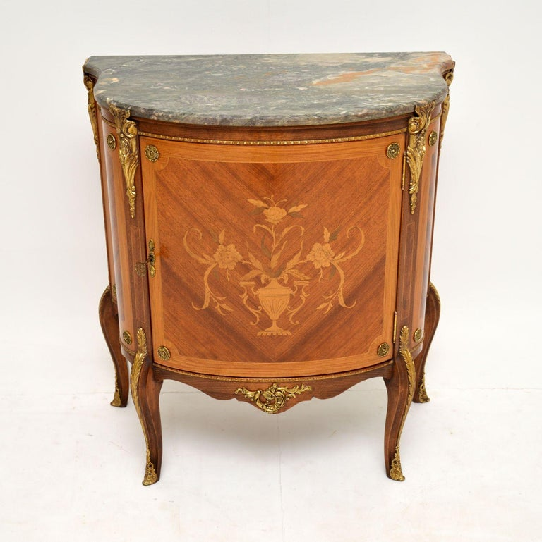 A beautiful marble top cabinet in the antique French style, this dates from around the 1920-30's.  It is of wonderful quality, with profuse inlaid marquetry of various woods, mainly on the door in the form of a bouquet of flowers. There are high
