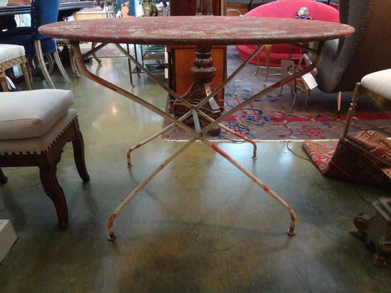 Gorgeous antique French folding iron garden table or bistro table with desirable chippy paint in soft orange-red and whites. This table would work well in an indoor garden room, family room or breakfast room.