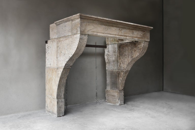 Beautiful robust and stately fireplace of French limestone from the 19th century. This antique fireplace is in Campagnarde style. The front part is decorated with various ornaments and the top has beautiful lines. The legs are slightly curved and
