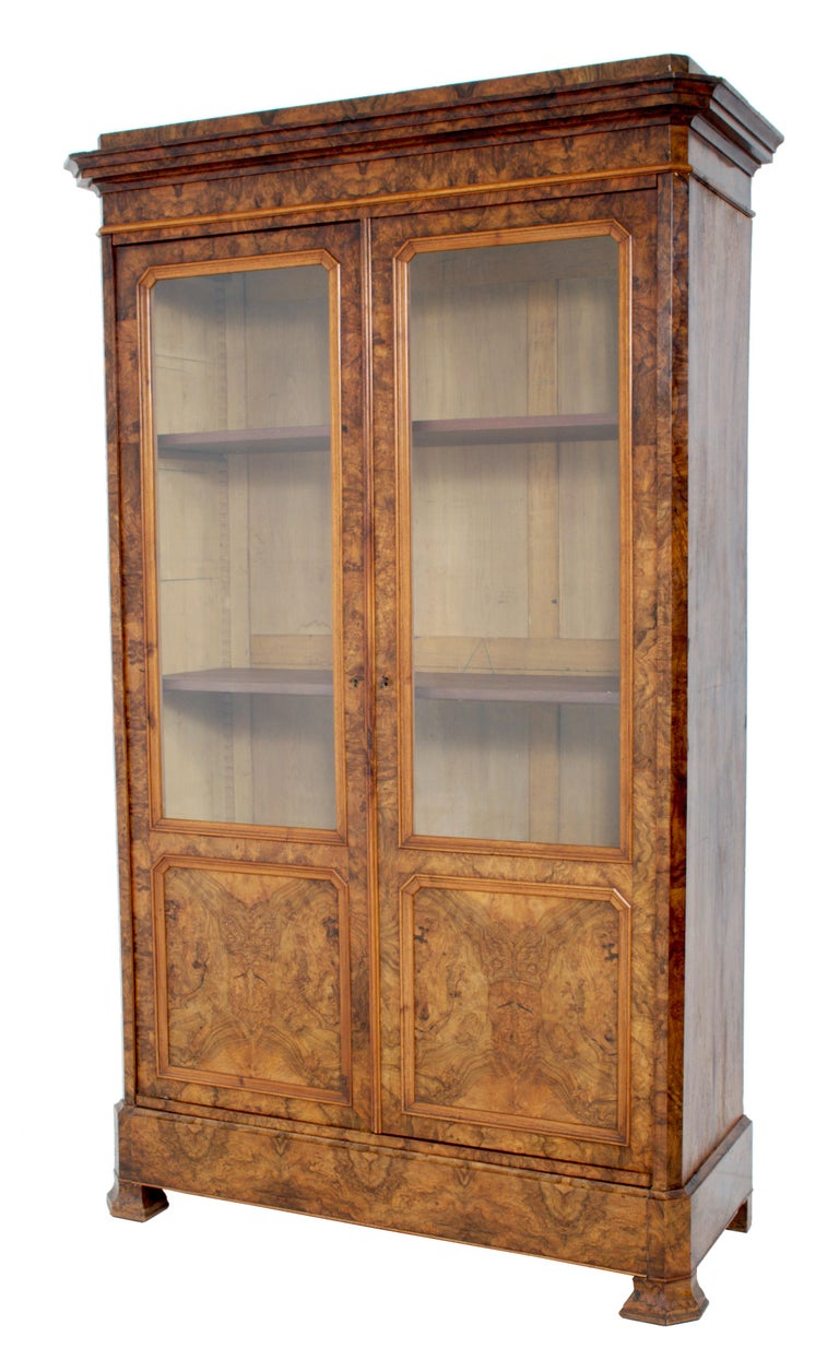 Antique French Louis Philippe burl walnut bookcase / cabinet, circa 1830. The bookcase having a stepped cornice with two doors below enclosing three adjustable shelves. The bookcase having a 'secret' drawer to the base, raised on bracket feet, and