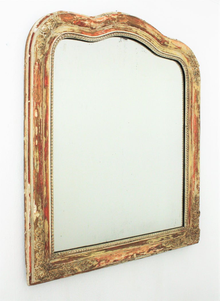 Louis Philippe mirror with finely carved floral details and terrific patinated parcel-gilt finish. France, circa 1840. The frame has parcel-gilt gold leaf accents and an amazing patina showing different coats of paints in shades of brown, orange