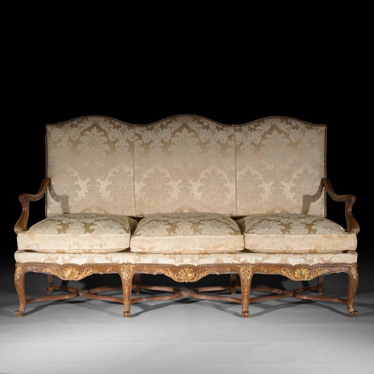 A fine French 19th century Louis XIV – Regence style oak and parcel-gilt sofa or settee,of well-shaped outline and desirable generous proportions.  Why we like it Itsextremely well drawn shape, Fine hand carved and gilded decoration make this