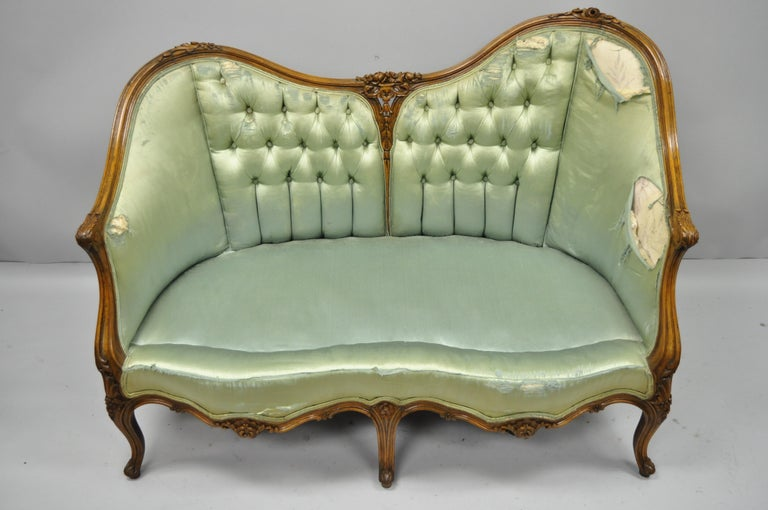 Antique French Louis XV Style carved walnut double hump back settee loveseat. Item features unique double hump back with one end slightly raised, tight solid frame, solid walnut construction, finely carved details, five cabriole legs, and great