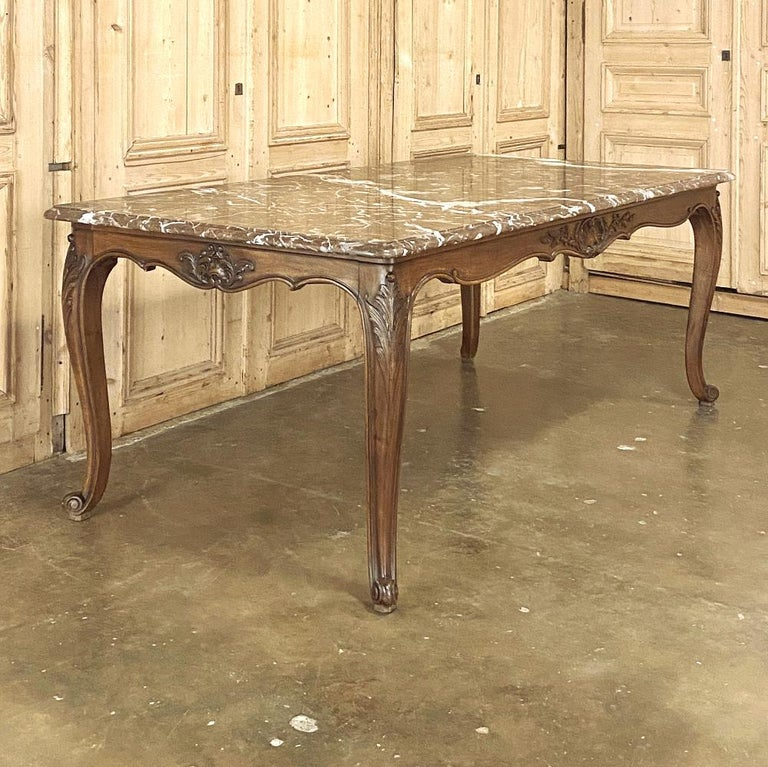 Antique French Louis XV walnut marble-top dining table is a truly unusual find! Sculpted from exquisite French walnut and luxuriously veined rouge marble, it combines the best of both worlds! The undulating scrollwork of the apron and cabriole legs