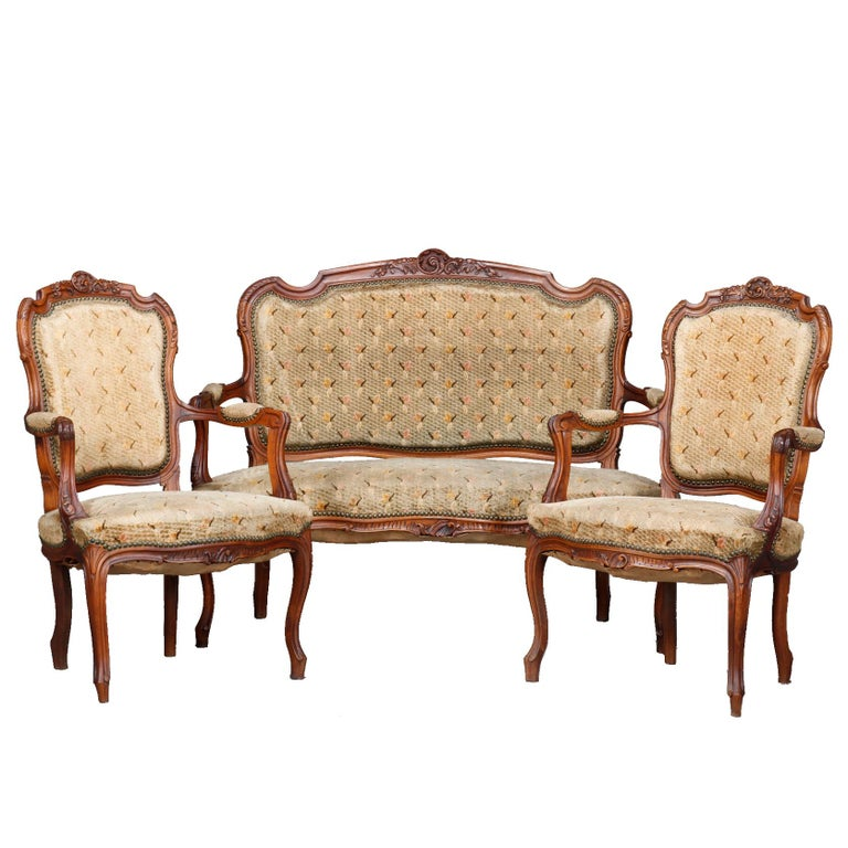 An antique French Louis XVI parlor set offers walnut construction with carved foliate crests, scroll arms and raised on cabriole les terminating in scroll feet; upholstered backs, seats and arms; set includes settee with two arm chairs, circa