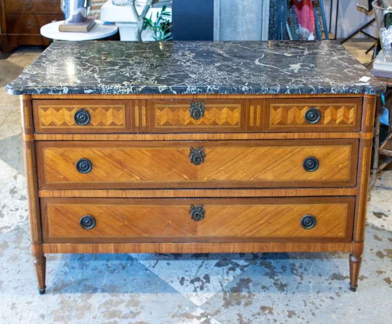 This beautifully decorated three-drawer commode features a Belgian marble top and stunning veneer marquetry on the drawer-fronts and sides. The top has rounded front corners and plenty of movement in the marble coloring. The hardware consists of