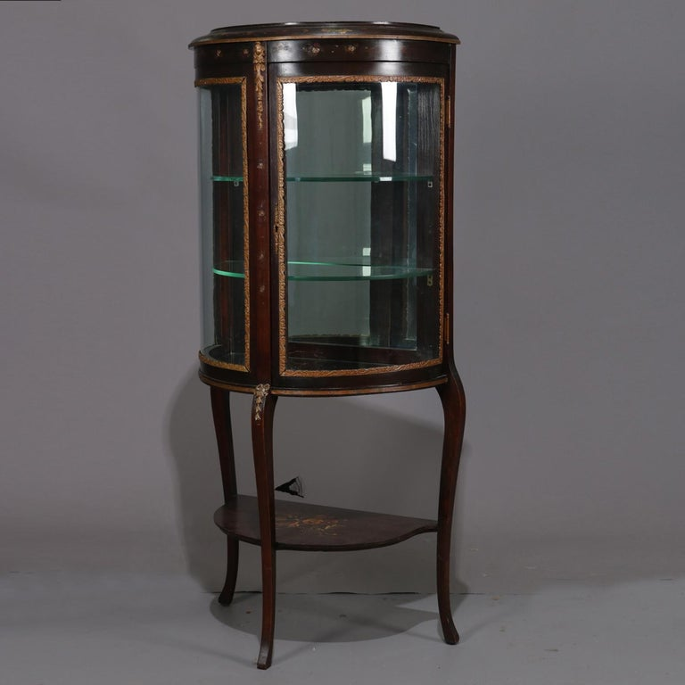 Antique French Louis XVI mahogany vitrine features Demilune form with bent glass and single door opening to mirrored interior with glass shelving, seated on cabriole legs, ormolu mounts and hand painted decoration throughout, circa