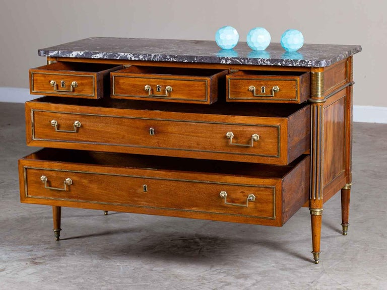 This Neoclassical Louis XVI period antique French walnut commode chest, circa 1790 has a marble top along with five drawers all embellished with brass detailing. The elegant simplicity of this late 18th century French chest of drawers results from
