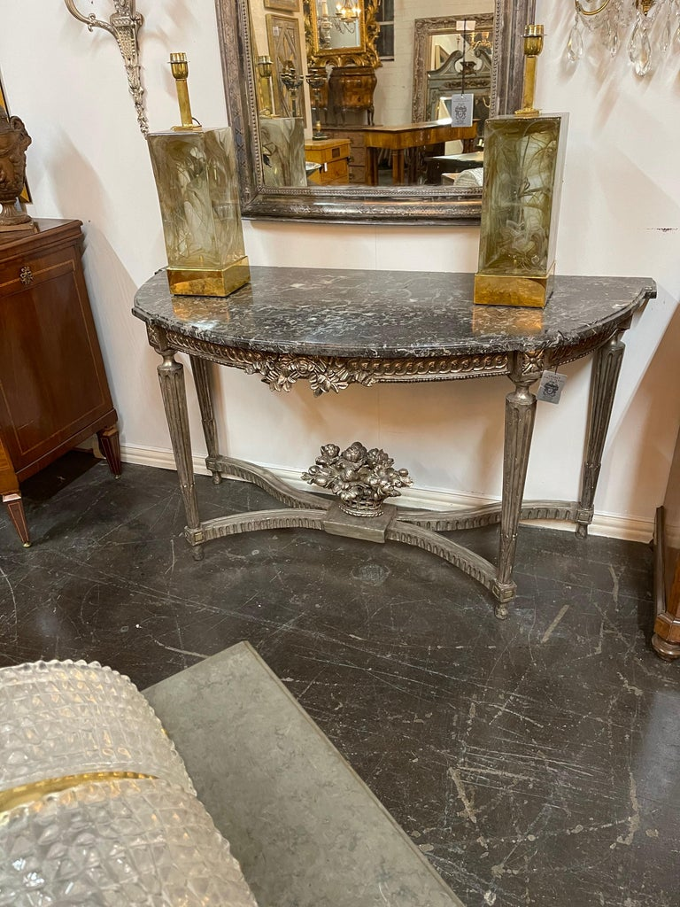 Superb 19th century French Louis XVI style silver gilt carved wood console table with a fine quality shaped marble top. The frieze nicely carved and centred by leaf accents.   The entire on tapering fluted legs held by a contoured stretcher
