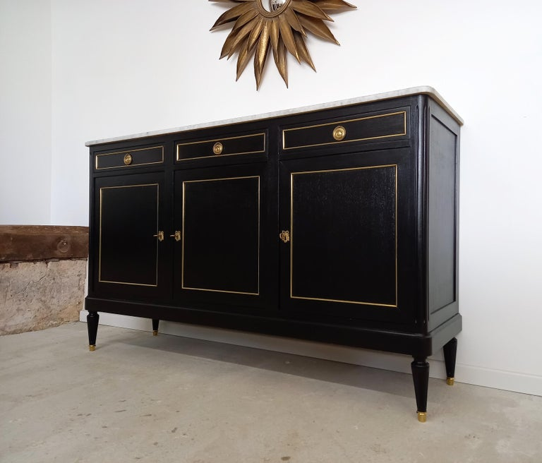 Antique French Louis XVI style buffet topped with a white Carrara marble, fluted legs finished with golden bronze clogs and thorough dressed in brass detail. Three dovetailed drawers, and doors with two removable shelves adjustable to the desired