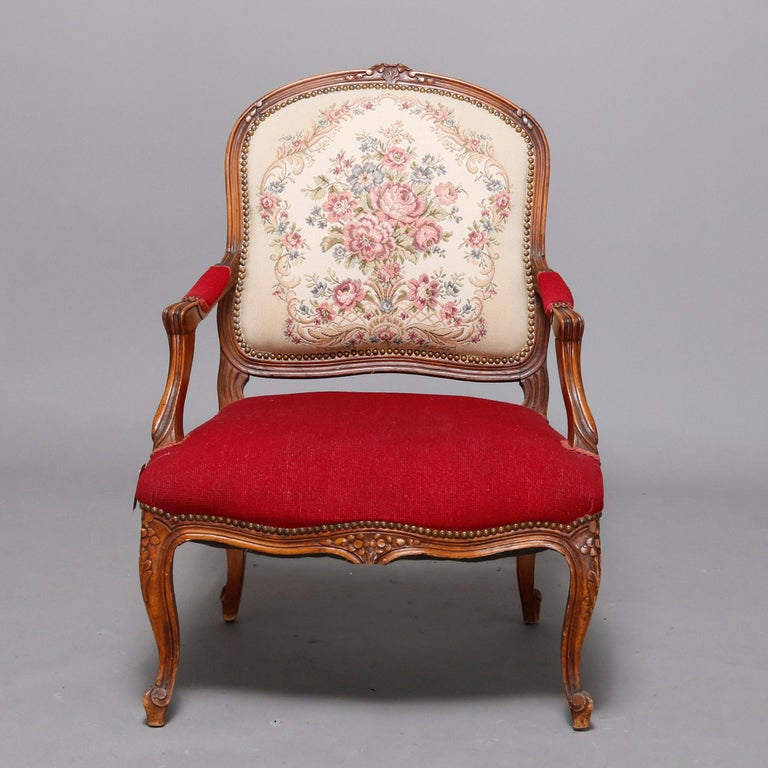 An antique French Louis XVI style armchair offers carved fruitwood frame with foliate crest surmounting medallion back with floral needlepoint upholstery surmounting covered arms and seat in complementing solid and raised on cabriole legs