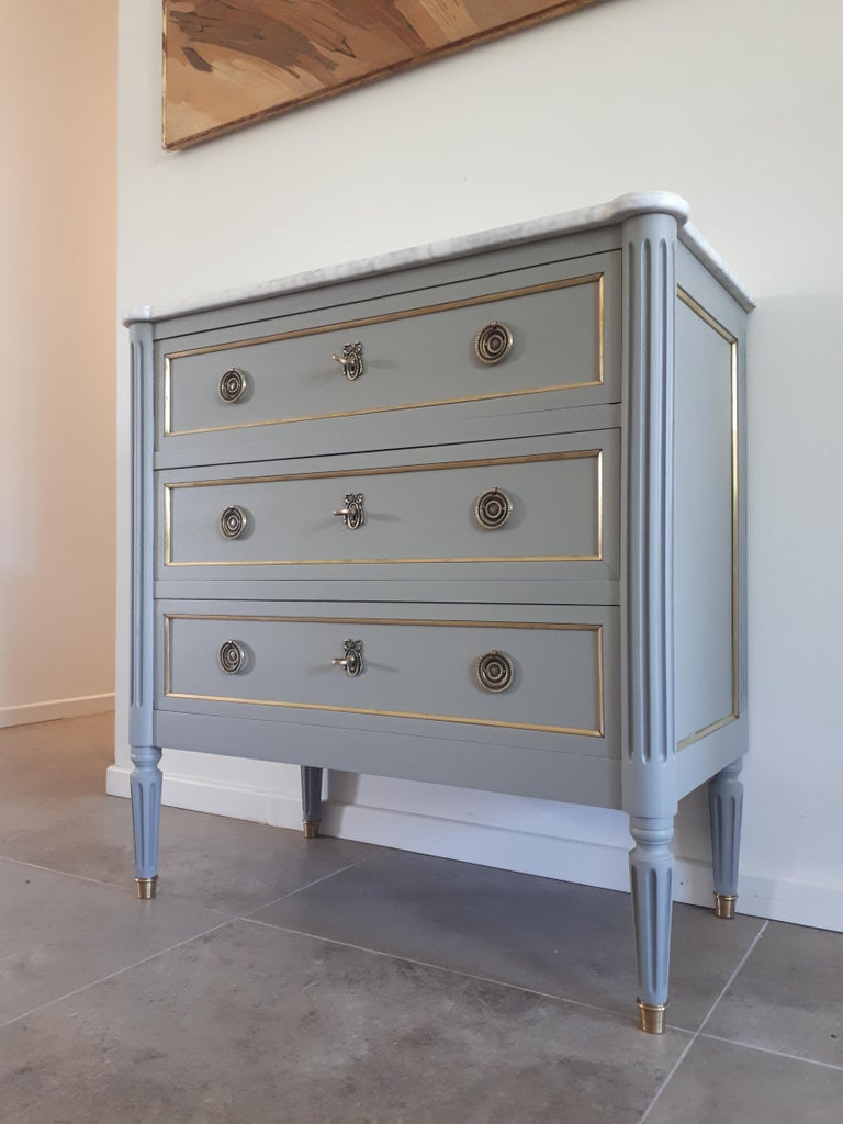 Antique French, Louis XVI style chest of drawers topped with a white Carrara marble, fluted legs finished with golden bronze clogs. 