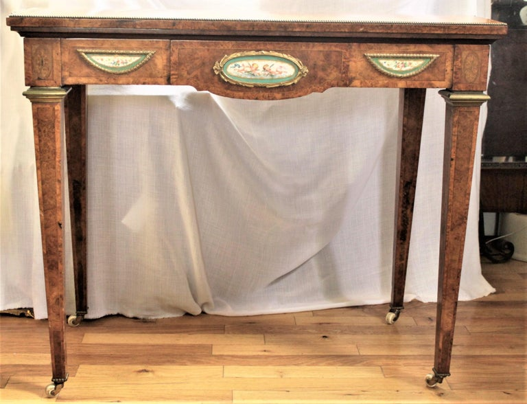 This very detailed and elaborate games or card table is unsigned, but presumed to have been made in England in circa 1850 in the French Louis XVI style. The table is done in extremely nice burled walnut, with a double banded serpentine top with nice