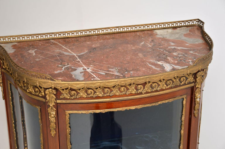 French antique Louis XV style mahogany display cabinet dating from circa 1880s-1890s period and in very good original condition.  It has a marble top with a gilt metal pierced gallery with swags below. There are gilt bronze mounts on the top, on