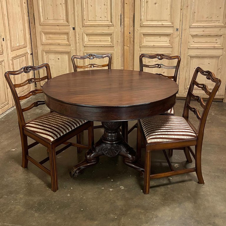 Napoleon III Period French Mahogany Empire Style Center Table features a round, tailored top which showcases the natural beauty of the exotic imported wood.  Support is provided by a center pedestal carved with urn and foliate motifs, supported by