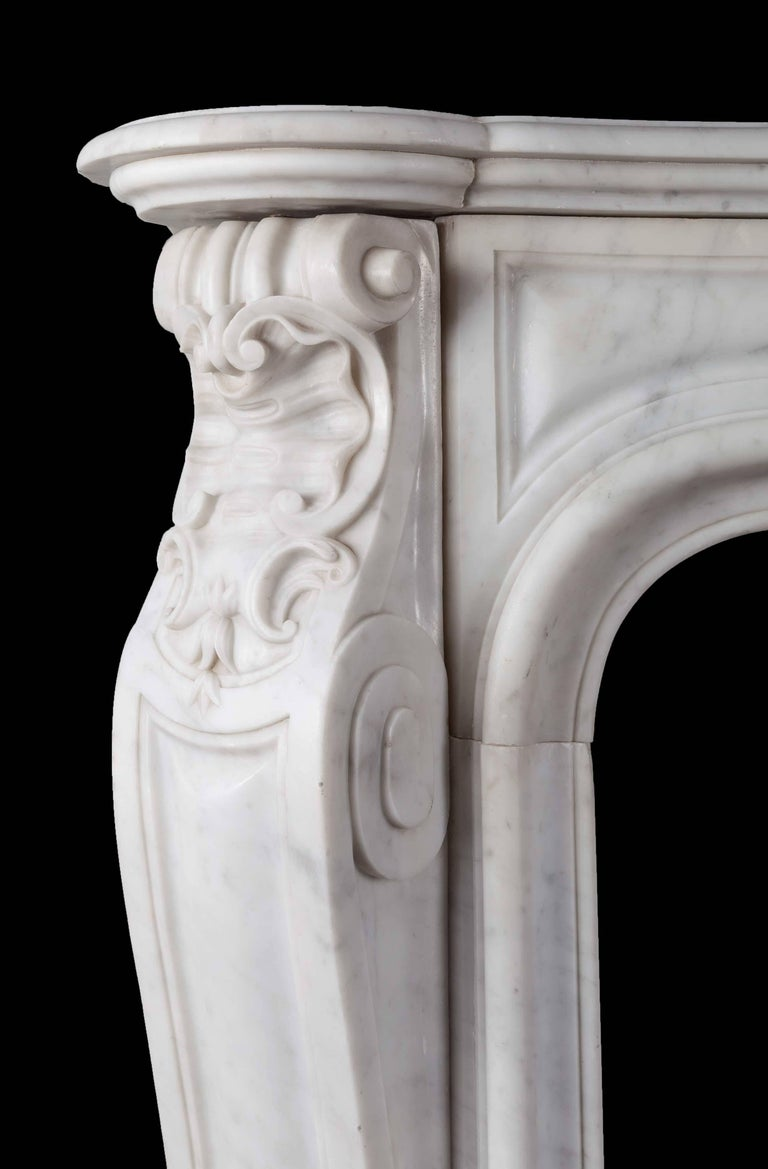 An antique French Carrara marble mantelpiece in the Louis XV style. The serpentine panelled frieze is centred by a large foliate cartouche, this is flanked by acanthus scrolled and angled jambs with scallop shell corners, all resting on curved