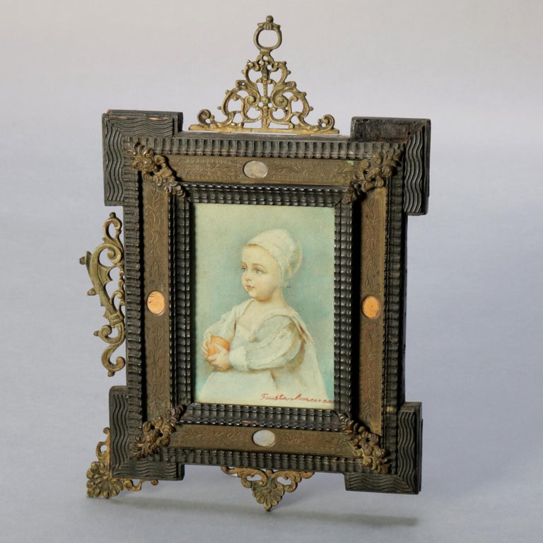 An antique French miniature watercolor painting depicts portrait of a baby and is signed illegible lower right, seated in Folk Art carved wood frame with floral incised inset and having foliate and scroll cast bronze accoutrements, 19th