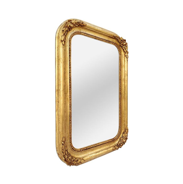 Antique french mirror with rounded edge of romantic style, circa 1830. Antique frame (width : 7 cm / 2.75 in.) with decor of flowers and foliages, pearls at the edge near the glass. Re-gilding to the patinated leaf. Modern glass mirror. Antique wood